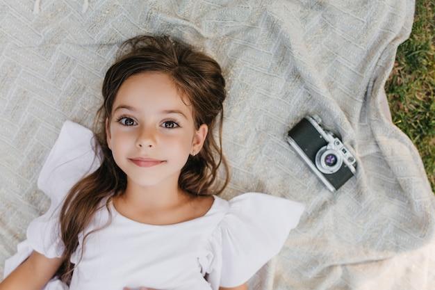 Zainspirowana Mała Dama O Dużych Brązowych Oczach Leżąca Na Kocu W Ogrodzie I Patrząca W Górę Z Delikatnym Uśmiechem. Ogólny Portret Ciemnowłosej Dziewczyny W Białej Sukni, Relaks Na Ziemi W Pobliżu Aparatu. Darmowe Zdjęcia