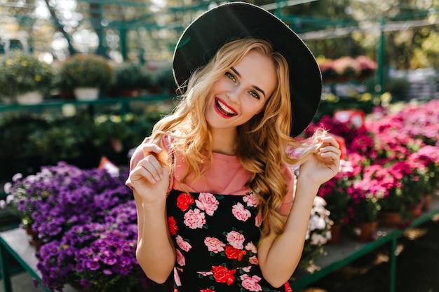 Zainspirowana Modelka W Kapeluszu Stojąca Na Froncie Kolorowych Kwiatów. Portret Atrakcyjnej Kobiety ślepy Relaks Na Oranżerii. Darmowe Zdjęcia