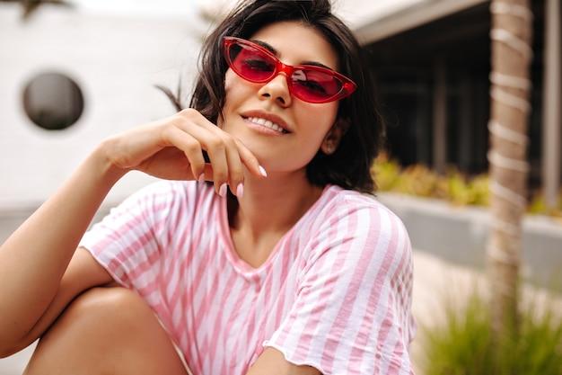Zainteresowana Uśmiechnięta Kobieta W T-shirt W Paski Patrząc Na Kamery. Zewnątrz Strzał Beztroskiej Opalonej Pani W Okularach Przeciwsłonecznych Na Tle Ulicy. Darmowe Zdjęcia