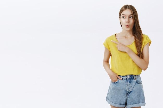 Zaintrygowana ładna Dziewczyna Wyglądająca Na Rozbawioną, Wskazując Palcem W Lewo Darmowe Zdjęcia