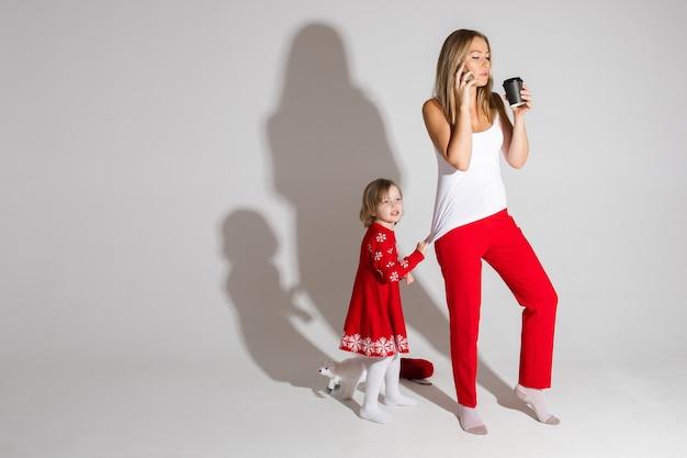 Zajęta Mama Rozmawiająca Przez Komórkę I Pijąca Kawę, Podczas Gdy Jej Córka W Czerwonej Sukience Ze świątecznym Wzorem Przyciąga Jej Uwagę. Premium Zdjęcia