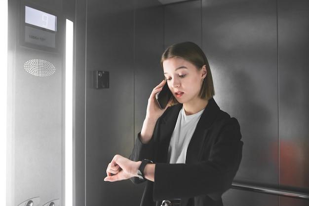 Zajęty Młody Bizneswoman Patrzy Na Zegarek I Rozmawia Przez Telefon W Windzie. Premium Zdjęcia