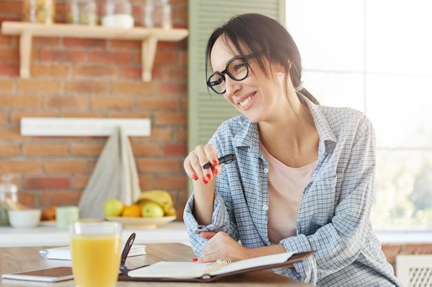 Zajęty Poranek Bizneswoman. Radośnie Uśmiechnięta Kobieta Wyraża Pozytywne Emocje, Jak Zapisuje Swój Harmonogram Pracy W Spiralnym Dzienniku, Darmowe Zdjęcia