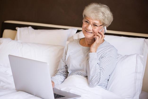 Zajęty Starszy Kobieta Pracująca W łóżku Darmowe Zdjęcia