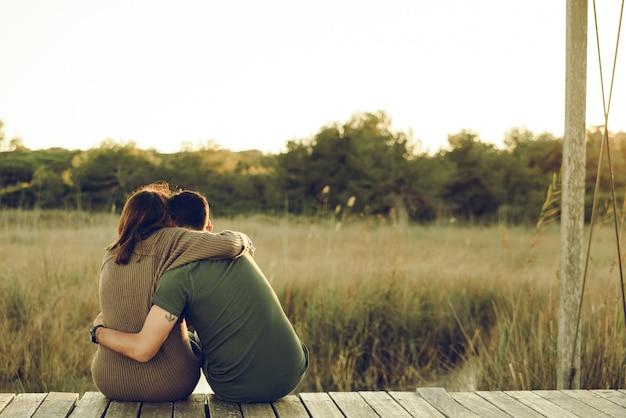 Zakochana Para Obejmowała Się Na Plecach, Aby Pogodzić Się I świętować Swoją Miłość, Siedząc W Naturze. Premium Zdjęcia