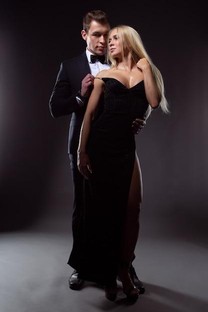 Zakochany Mężczyzna W Garniturze Delikatnie Obejmuje Seksowną Młodą Blondynkę W Wieczorowej Sukni Premium Zdjęcia