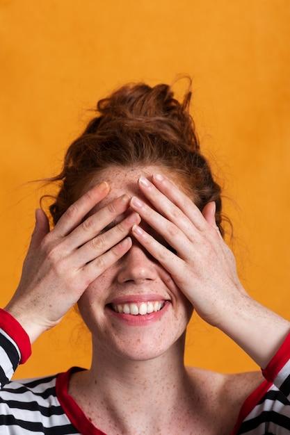 Zakończenia smiley kobieta z pomarańczowym tłem zakrywa ona oczy Darmowe Zdjęcia
