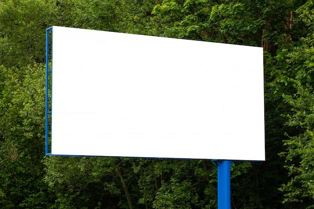 Zakończenie biały pusty billboard przeciw zielonemu lasowi wzdłuż drogi Premium Zdjęcia