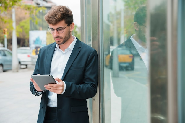 Zakończenie biznesmen opiera blisko szklanego drzwi używać cyfrową pastylkę Darmowe Zdjęcia
