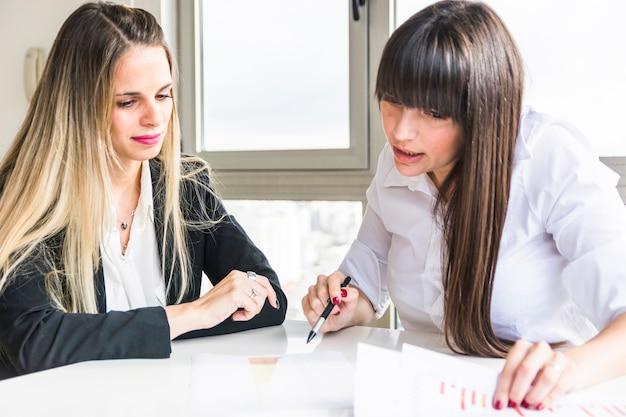 Zakończenie bizneswomany analizuje biznesowego raport w biurze Darmowe Zdjęcia