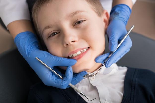 Zakończenie chłopiec ma jego zęby egzamininujących dentystą Premium Zdjęcia