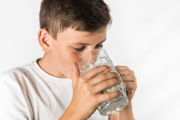 Zakończenie chłopiec pije mleko w szkle przeciw białemu tłu Darmowe Zdjęcia