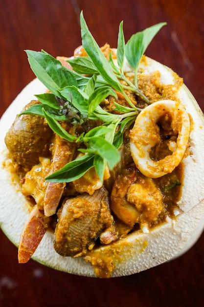 Zakończenie Curry Lejący Się Owoce Morza W Kokosowej Filiżance Premium Zdjęcia