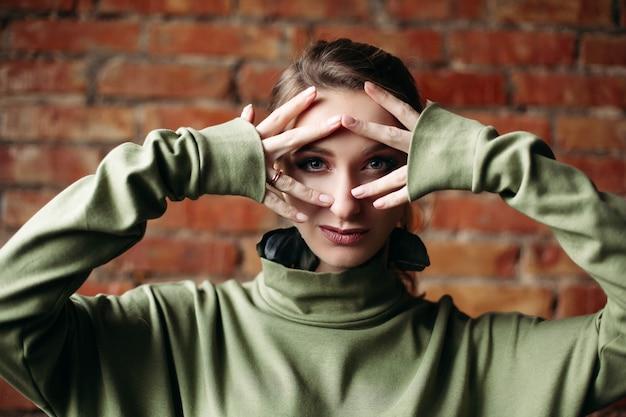 Zakończenie Dziewczyna Jest Ubranym W Khakiej Sukni Macania Twarzy Twarzy Palcami, Pozuje Przeciw ściana Z Cegieł. Premium Zdjęcia