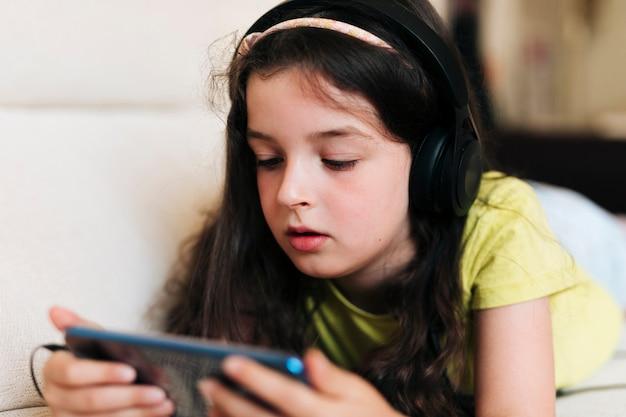 Zakończenie dziewczyna patrzeje telefon z hełmofonami Darmowe Zdjęcia