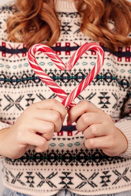 Zakończenie dziewczyna trzyma cukierki z pulowerem Darmowe Zdjęcia