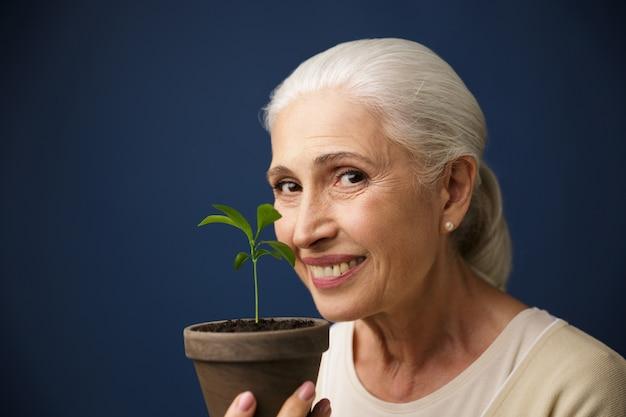 Zakończenie Fotografia Szczęśliwa Starzejąca Się Kobieta Pokazuje Młodej Rośliny W Miejscu Darmowe Zdjęcia