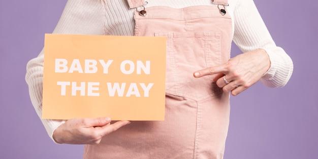 Zakończenie Kobieta W Ciąży Wskazuje Przy Papierem Z Dzieckiem Na Sposób Wiadomości Darmowe Zdjęcia