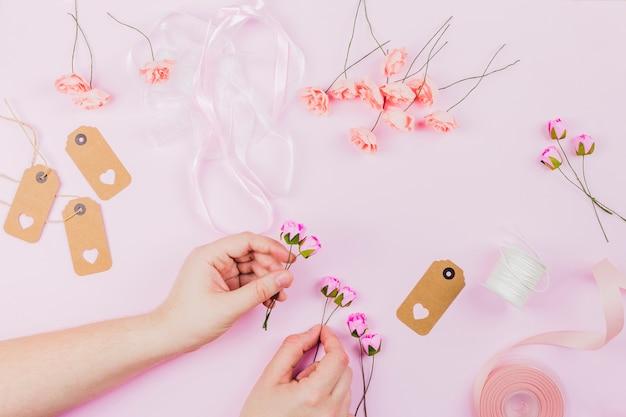 Zakończenie Kobiety Ręka Układa Kwiatu Z Faborkiem I Etykietkami Na Różowym Tle Darmowe Zdjęcia