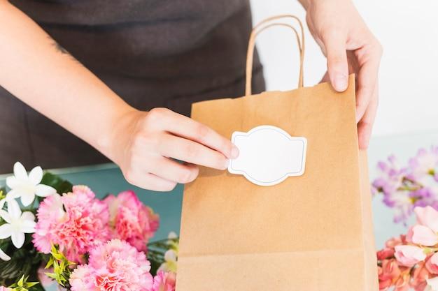 Zakończenie Kobiety Ręki Klejenia Etykietka Na Papierowej Torbie Premium Zdjęcia