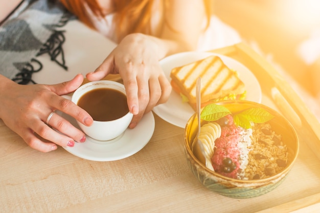 Zakończenie kobiety ręki mienia puchar oatmeal z owoc na tacy Darmowe Zdjęcia