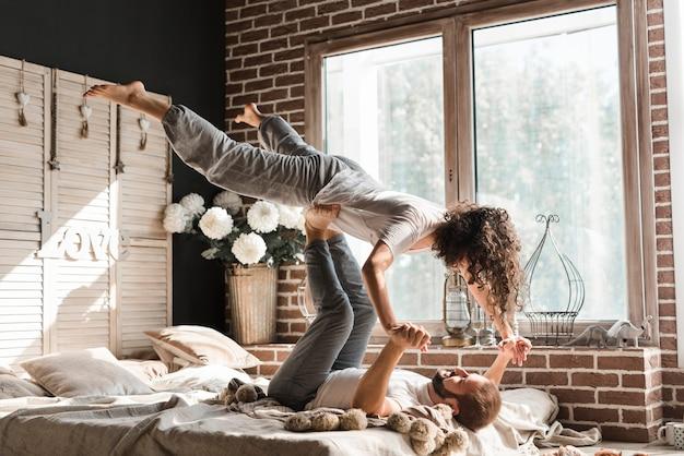 Zakończenie kobiety równoważenia mężczyzna cieki na łóżku w domu Darmowe Zdjęcia