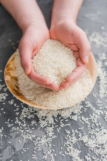 Zakończenie ludzka ręka trzyma adra niegotowany biały jaśminowy ryż Darmowe Zdjęcia