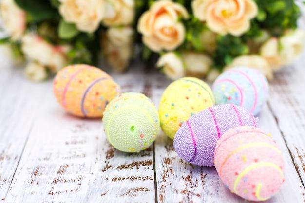Zakończenie malujący jajka z kwiatami na białym tle Premium Zdjęcia