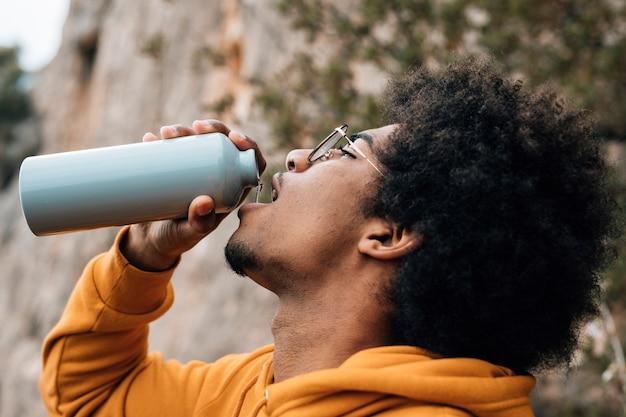 Zakończenie męski wycieczkowicz pije wodę od butelki Darmowe Zdjęcia