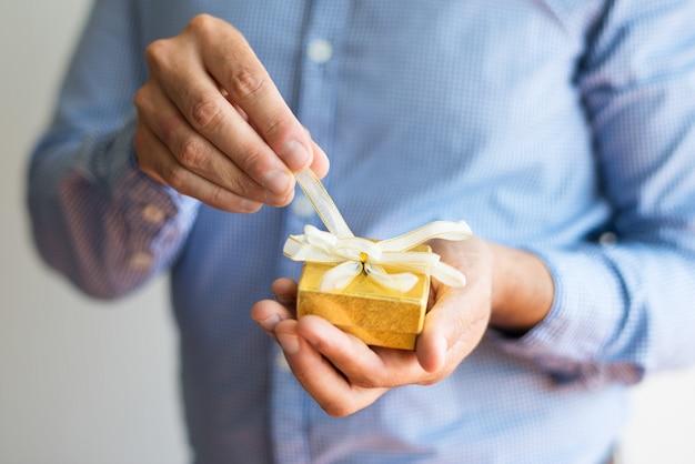 Zakończenie mężczyzna odsupłuje łęk na małym żółtym pudełku Darmowe Zdjęcia