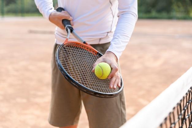 Zakończenie mężczyzna trzyma tenisową piłkę na kancie Darmowe Zdjęcia