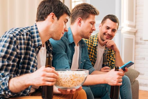 Zakończenie młodzi człowiecy siedzi na kanapie patrzeje smartphone Darmowe Zdjęcia