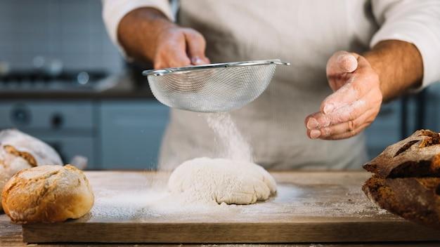 Zakończenie piekarz przesiewanie pszeniczna mąka przez sito nad ciastem Darmowe Zdjęcia