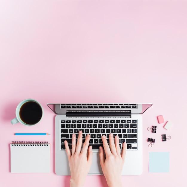 Zakończenie pisać na maszynie na laptopie z stationeries i filiżanką na różowym tle ręka Darmowe Zdjęcia