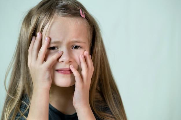 Zakończenie Portret Nieszczęśliwa Mała Dziewczynka Z Długie Włosy Zakrywa Jej Twarz Z Ręki Płakać. Premium Zdjęcia