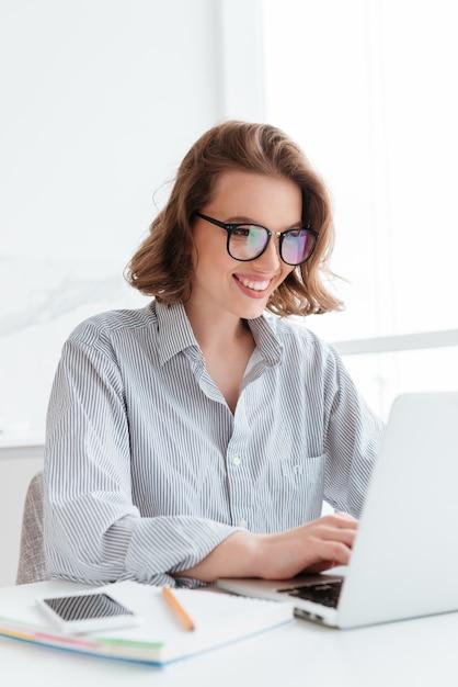 Zakończenie Portret Rozochocona Bunette Kobieta W Szkłach Używać Laptop Podczas Gdy Pracujący W Domu Darmowe Zdjęcia