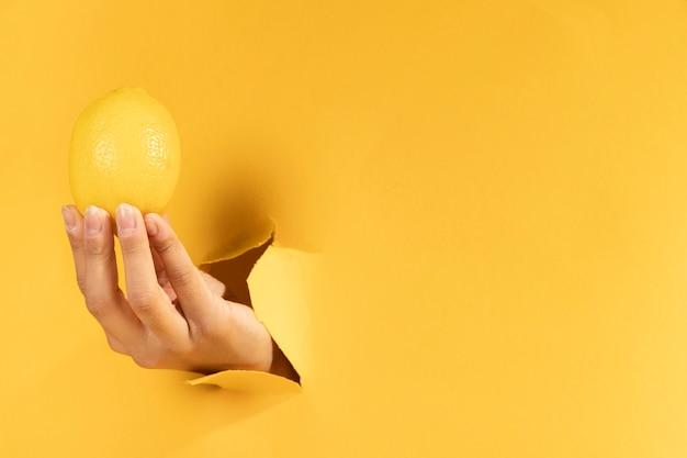 Zakończenie ręka z cytryny i kopii przestrzenią Darmowe Zdjęcia