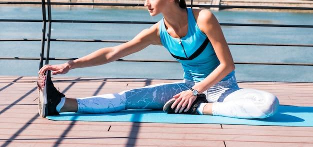 Zakończenie rozciąga jej ręki i nogi obsiadanie na ćwiczenie macie kobieta Darmowe Zdjęcia