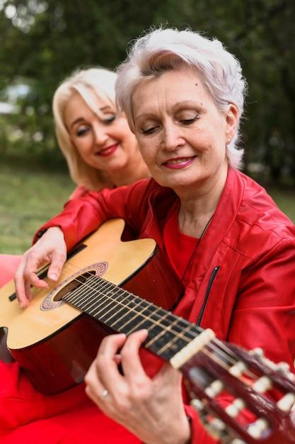 Zakończenie starsza kobieta bawić się gitarę Darmowe Zdjęcia