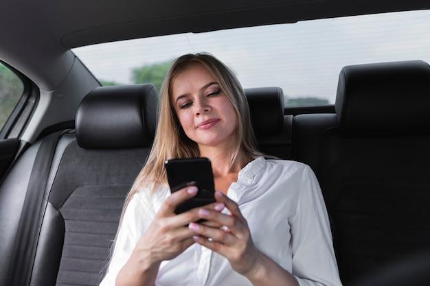 Zakończenie strzelał z blondynki kobietą patrzeje telefon Darmowe Zdjęcia