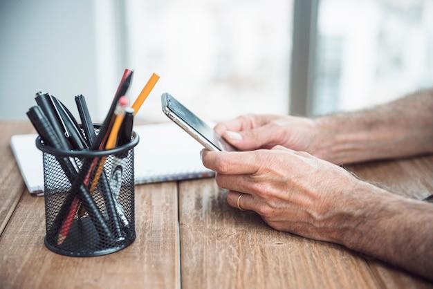Zakończenie trzyma mądrze telefon w ręce nad drewnianym biurkiem mężczyzna ręka Darmowe Zdjęcia