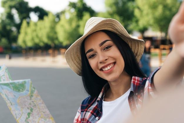 Zakończenie u uśmiechnięta kobiety mienia mapa i brać selfie przy outdoors Darmowe Zdjęcia