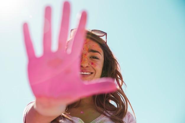 Zakończenie Uśmiechnięta Młoda Kobieta Pokazuje Jej Malującą Różową Rękę Darmowe Zdjęcia