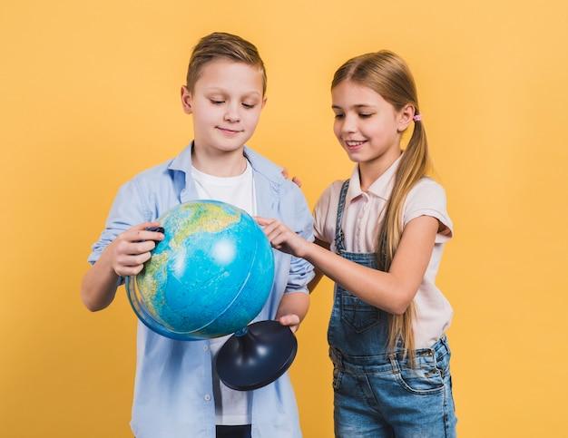 Zakończenie uśmiechniętej dziewczyny macanie przy kula ziemska chwytem jej przyjaciel stoi przeciw żółtemu tłu Darmowe Zdjęcia
