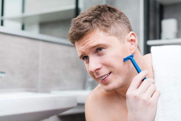 Zakończenie Uśmiechnięty Młody Człowiek Golenie Z Błękitną żyletką W łazience Darmowe Zdjęcia