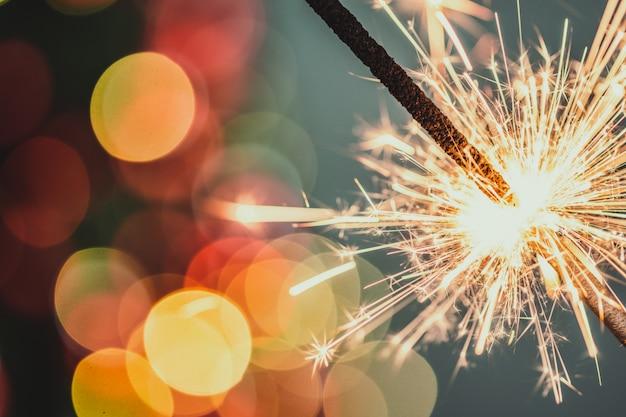 Zakończenie Wakacyjny Bożenarodzeniowy Sparkler Na Ciemnym Tle Premium Zdjęcia