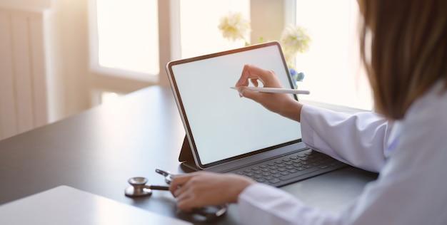 Zakończenie Widok Młodej Kobiety Lekarka Pisze Medycznych Mapach Z Pastylką W Biurowym Pokoju Premium Zdjęcia