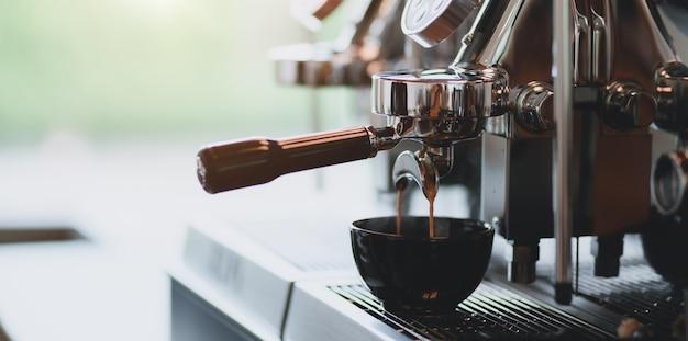 Zakończenie widok nalewa espresso od ekspresu do kawy kawy espresso w filiżankę Premium Zdjęcia