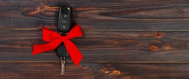 Zakończenie widok samochodów klucze z czerwonym łękiem jak teraźniejszy na drewnianym tle Premium Zdjęcia