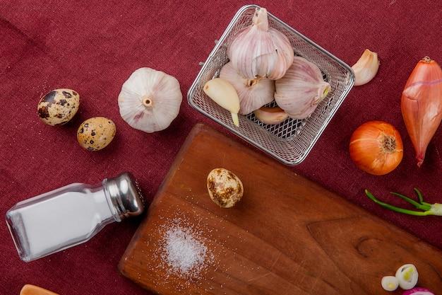 Zakończenie Widok Warzywa Jako Czosnku Jajeczna Cebula Z Solą I Tnąca Deska Na Burgundy Tle Darmowe Zdjęcia